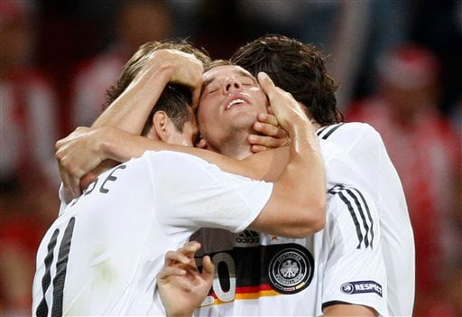 Germany's Lukas Podolski, center, is hugged by his teammates Miroslav Klose, left, and Mario Gomez, right, after scoring the opening goal during the group B match between Germany and Poland in Klagenfurt, Austria.