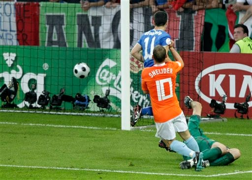 Netherlands' Wesley Sneijder, foreground, scores the 2nd goal past Italy's Gianluigi Buffon, bottom right, and Antonio Di Natale, during the group C match between the Netherlands and Italy in Bern, Switzerland.