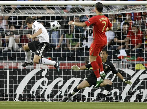 Germany's Miroslav Klose, left, scores his side's 2nd goal past Portugal's Ricardo,rear right, and Cristiano Ronaldo during the quarterfinal match between Portugal and Germany in Basel, Switzerland.