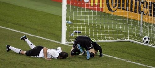 Germany's Christoph Metzelder, left, and goalie Jens Lehmann lie on the pitch as the goal heads into the net, after Portugal's Nuno Gomes, unseen, shot to score his team's first goal during the quarterfinal match between Portugal and Germany in Basel, Switzerland.