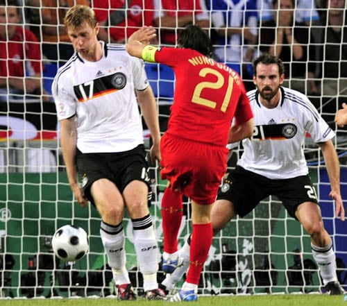 Portugal's Nuno Gomes, center, scores his teams first goal for Portugal, against Germany's Per Mertesacker, left, and Christoph Metzelder, right, during the Euro 2008 European Soccer Championship quarterfinal match between Portugal and Germany in Basel, Switzerland.