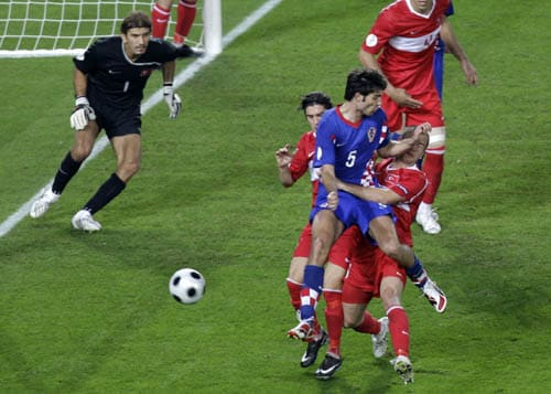 Croatia's Vedran Corluka, front, and Turkey's Emre Asik challenge for the ball as Turkey's Rustu Recber, left, looks on during the quarterfinal match between Croatia and Turkey in Vienna, Austria.