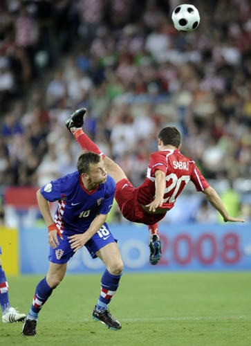Turkey's Sabri Sarioglu, right, and Croatia's Ivica Olic challenge for the ball during the quarterfinal match between Croatia and Turkey in Vienna, Austria.