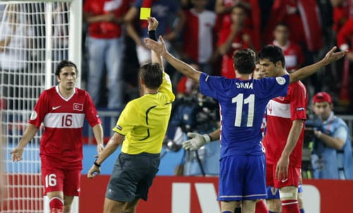 Referee Roberto Rosetti from Italy, second left, awards a yellow card to Turkey's Ugur Boral, left, during the quarterfinal match between Croatia and Turkey in Vienna, Austria.