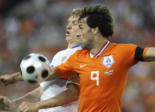 Netherlands' Ruud van Nistelrooy, foreground, challenges for the ball with Russia's Denis Kolodin during the quarterfinal match between the Netherlands and Russia in Basel, Switzerland.