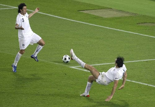 Italy's Luca Toni, bottom, goes for the ball as Fabio Grosso looks on during the quarterfinal match between Spain and Italy in Vienna, Austria.