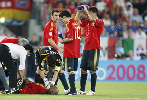 Spain's Marcos Senna, bottom, is attended during the extra-time of the quarterfinal match between Spain and Italy in Vienna, Austria.