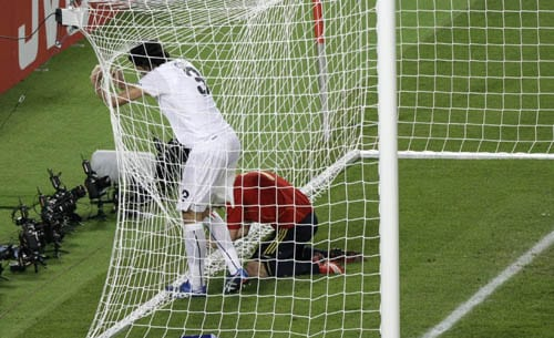 Italy's Fabio Grosso, left, and Spain's David Villa grab the net of a goal during the quarterfinal match between Spain and Italy in Vienna, Austria.