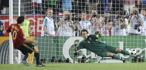 Spain's Cesc Fabregas, left, scores the decisive goal during the penalty shootout of the quarterfinal match between Spain and Italy in Vienna, Austria.