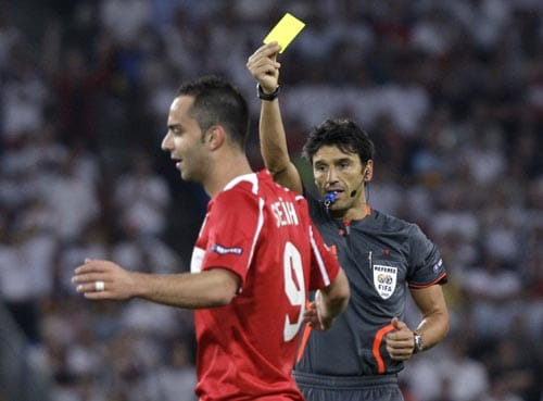 Referee Massimo Busacca from Switzerland, right, awards the yellow card to Turkey's Semih Senturk during the semifinal match between Germany and Turkey in Basel.