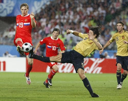 Russia's Roman Pavlyuchenko, left, and Spain's Carles Puyol challenge for the ball during the semifinal match between Russia and Spain in Vienna, Austria.