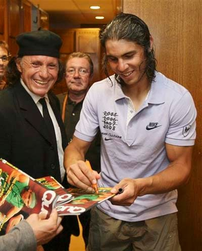 Rafael Nadal signs autographs in the locker room after defeating Switzerland's Roger Federer during the men's final at the French Open tennis tournament in Paris. (AP)