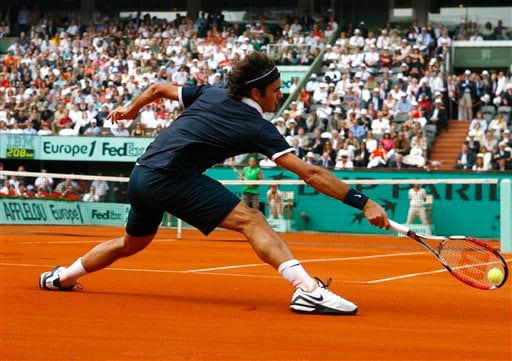 Roger Federer stretches to make a return to Rafael Nadal during the French Open final. (AP)