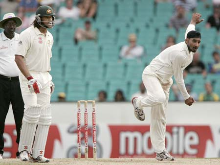 Australia's Andrew Symonds, second left, watches India's Harbhajan Singh, right, bowl at the Sydney Cricket Ground on the fourth day of their second cricket test.