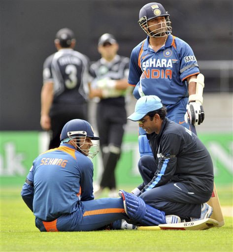 Virender Sehwag receives treatment to a leg injury whlie teammate Sachin Tendulkar stands near by during the 2nd One-Day International against New Zealand at Westpac Stadium in Wellington (AP Photo)
