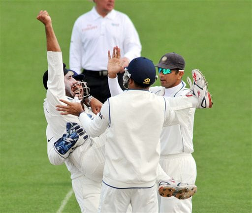India's Harbhajan Singh is lifted by MS Dhoni as his teammates celebrate his fifth wicket on 4th day of the 1st Test in Hamilton on Saturday. (AP Photo)