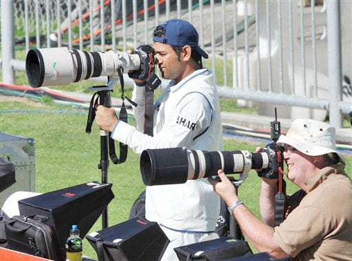 Injured Indian captain MS Dhoni joins the photographers in the match against New Zealand on the 2nd day of the 2nd Test at McLean Park in Napier on Friday. (AP Photo)