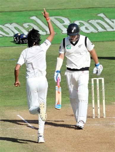 India's Ishant Sharma runs past New Zealand's Daniel Vettori after being caught behind by MS Dhoni on the second day of their 3rd Test at Basin Reserve in Wellington on Saturday. (AP Photo)