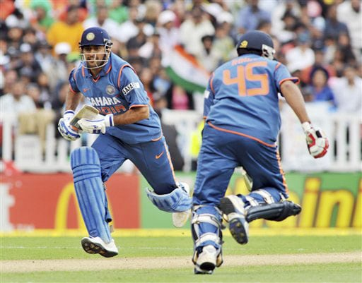 India's MS Dhoni crosses with Rohit Sharma against New Zealand on the 5th ODI match at Auckland on Saturday. (AP Photo)