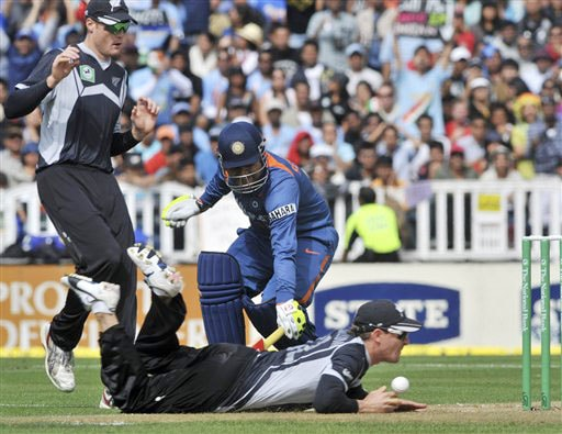 Brendon McCullum slides in as Virender Sehwag makes his ground in the 5th ODI match at Auckland on Saturday. (AP Photo)