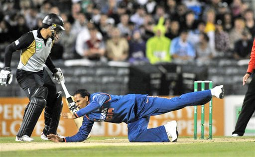 Yusuf Pathan attempts to field off his own bowling in front of Ross Taylor in the first Twenty20 International at Christchurch on Wednesday. (AP Photo)