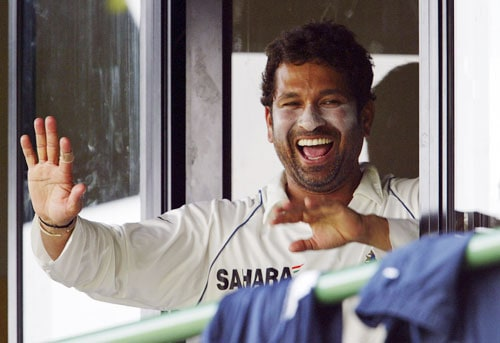 Sachin Tendulkar shares a light moment as he waves to spectators from the dressing room during the final day of a three day practice match between Sri Lanka A team and India in Colombo, Sri Lanka on July 20, 2008.