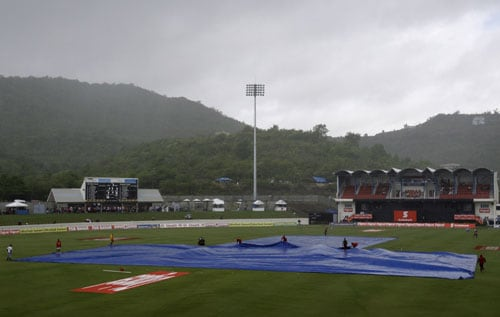 Ground keepers cover the pitch as a rain fall delays the start of the fourth and final One-Day International match between India and the West Indies at Beausejour in St. Lucia. (AP Photo)