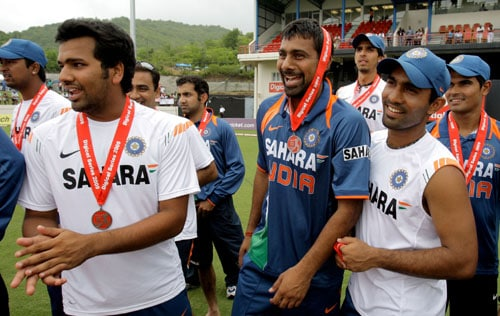 India's cricket players, from left, Rohit Sharma, Praveen Kumar, and Dinesh Karthik, celebrate after winning the One-Day International series against the West Indies at Beausejour in St. Lucia. (AP Photo)