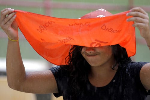 A cricket fan reacts with disappointment as rain fall during the fourth and final One-Day International match between India and the West Indies at Beausejour in St. Lucia. (AP Photo)