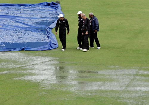 Cricket umpires Nigel Llong, Clyde Duncan, Goaland Greaves and Clancy Mack inspect the pitch before declaring the abandonment due to weather of the fourth and final One-Day International match between India and the West Indies at Beausejour in St. Lucia. (AP Photo)