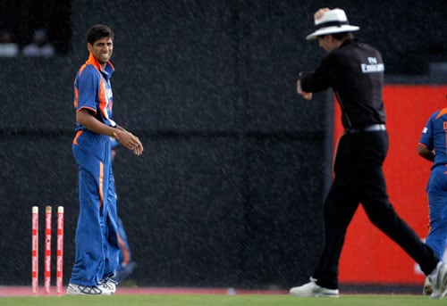 Ashish Nehra looks to the umpire Nigel Llong as he's calling to stop playing during a rain fall in the fourth and final One-Day International match against the West Indies at Beausejour in St. Lucia. (AP Photo)