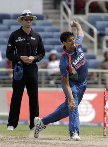 Ashish Nehra bowls against the West Indies, as umpire Nigel Llong looks on, during the first ODI against the West Indies at the Sabina Park. (AP Photo)