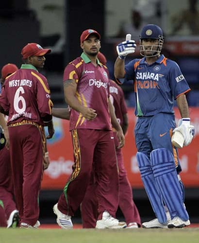 Mahendra Singh Dhoni gives a thumbs up to the fans as Ravi Rampaul and Shivnarine Chanderpaullook on, after winning the third ODI at Beausejour Cricket Ground, in Gros-Islet, St. Lucia on July 3, 2009. (AP Photo)