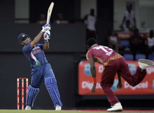 Mahendra Singh Dhoni drives for a six off bowler Jerome Taylor during the third ODI at Beausejour ground in Gros-Islet, St Lucia. (AP Photo)