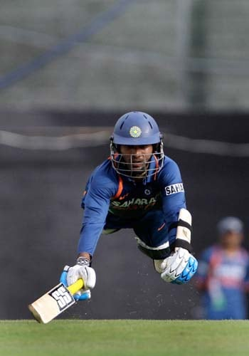 Dinesh Karthik dives to avoid a runout attempt by the West Indies' during the third ODI at Beausejour ground. (AP Photo)