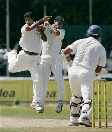 Nuwan Kulasekera, left, and fielder Thilan Samaraweera collide as they try to stop the ball, while Indian batsman Rahul Dravid looks on during the third day's play of the first Test cricket match between Sri Lanka and India in Colombo on Friday July 25, 2008.