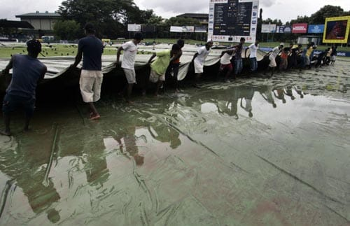 Ground staff at Colombo's SSC Stadium move the covers after overnight rain delayed the start of the first Test between India and Sri Lanka on Wednesday.