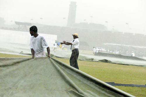 Curator of Galle International Cricket Ground Jayananda Warnaweera instructs ground staff to cover the ground as rain pours during the first day of the second Test between India and Sri Lanka in Galle on July 31, 2008.