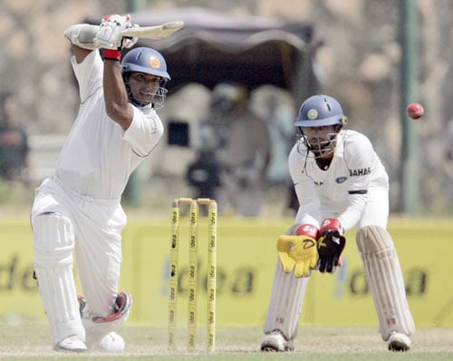 Kumar Sangakkara bats as Dinesh Karthik looks on during second day of the second Test match between India and Sri Lanka in Galle on August 1, 2008. (AP Photo)