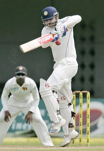 Virender Shewag bats as Sri Lankan captain Mahela Jayawardene looks on during the first day of the third Test between India and Sri Lanka in Colombo on August 8.