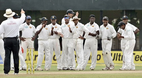 Sri Lankan cricketers celebrate as a ruling from the third umpire declares Gautam Gambhir (unseen) dismissed during the first day of the third Test between India and Sri Lanka in Colombo on August 8.