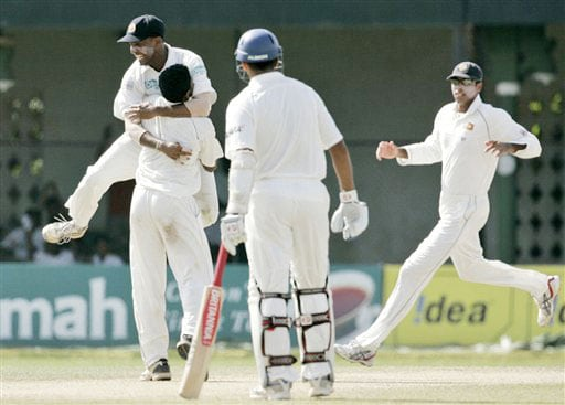 Thilan Samaraweera hugs Dhammika Prasad as Michael Vandort and Rahul Dravid look on during the third day's play of the final Test in Colombo on August 10, 2008.