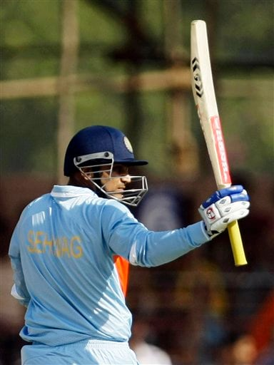 Indian batsman Virender Sehwag raises his bat to acknowledge the applause after he scored a half-century during the first ODI match between India and England in Rajkot on Friday. (AP Photo)
