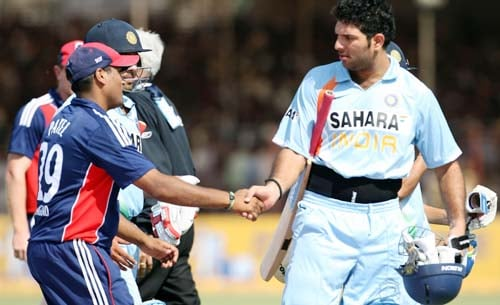 England's Samit Patel congratulates Indian batsman Yuvraj Singh for scoring his century during the first ODI between India and England in Rajkot on Friday. (AFP Photo)