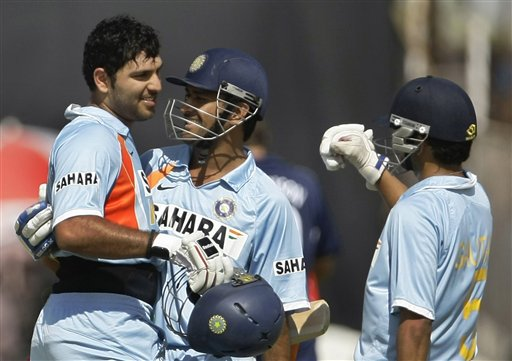 Indian batsman Yuvraj Singh is congratulated by Indian captain MS Dhoni, after scoring a century as team-mate Gautam Gambhir who was running for Yuvraj, comes in to congratulate him during their first ODI match against England in Rajkot on Friday. (AP Photo)