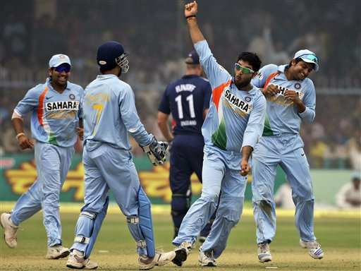 India bowler Yuvraj Singh celebrates as Rohit Sharma, MS Dhoni and Suresh Raina run to congratulate him for dismissing England batsman Ravi Bopara during the third ODI between India and England in Kanpur on Thursday. (AP Photo)
