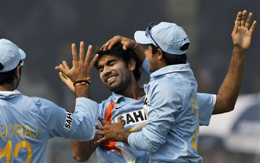India's Suresh Raina and Yuvraj Singh congratulate bowler Munaf Patel for dismissing England batsman Ian Bell during the third ODI India and England in Kanpur on Thursday. (AP Photo)
