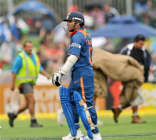 Sachin Tendulkar leaves the pitch as the grounds men bring on the covers when rained stopped play against New Zealand in their 1st one-day international match at McLean Park in Napier on Tuesday, March 3, 2009. (AP Photo)