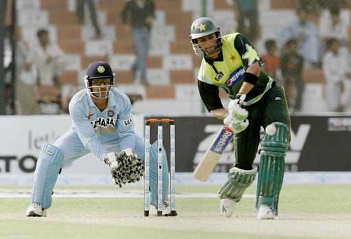 Shoaib Malik plays a shot as Indian wicketkeeper Mahandra Singh Dhoni looks on during their Asia Cup match at National Stadium in Karachi, Pakistan on June 26, 2008.