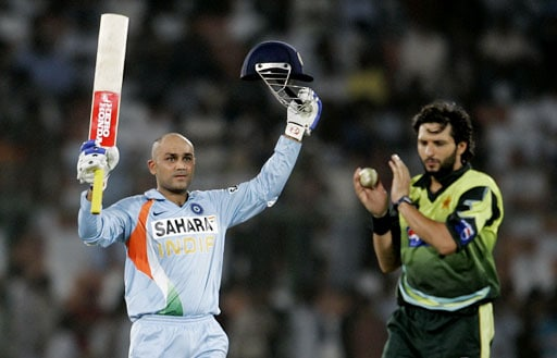 Virender Sehwag reacts after he reached his century, as Pakistani all-rounder Shahid Afridi claps, during their Asia Cup match at National Stadium in Karachi, Pakistan on June 26, 2008.